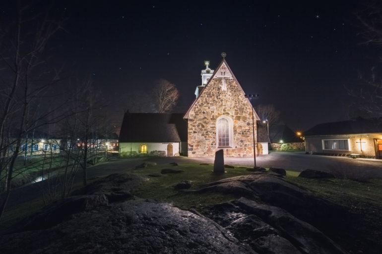 Pyhän Ristin kirkko valaistuna iltahämärässä.